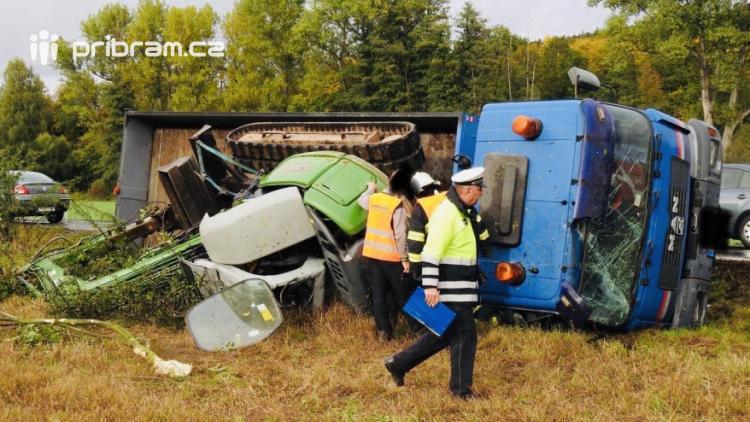 Nákladní vůz skončil na boku, řidič zdemoloval i převážený bagr